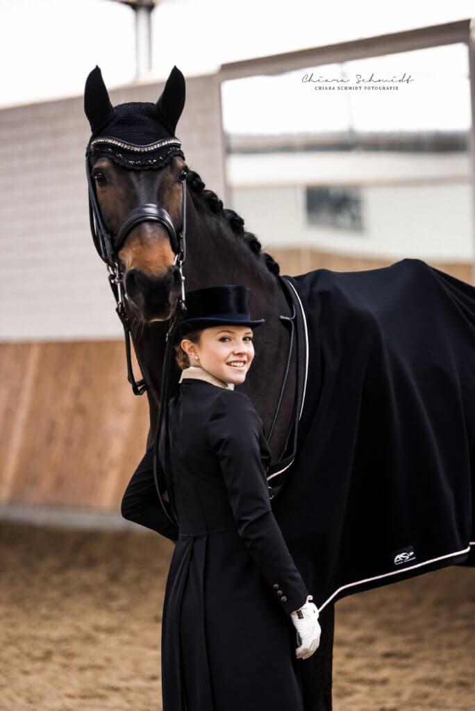 Junge Frau steht vor Dressurpferd und schaut lachend in die Kamera
