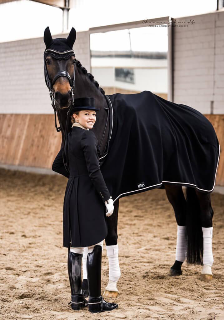 Junge Frau mit Frack und Zylinder hält ein Dressurpferd fest. Eine Reiter&Ross Decke liegt auf dem Pferd.