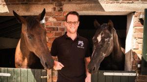 2 Dressurpferde stehen links und rechts von jungem Mann